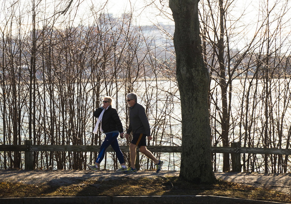 Two people take advantage of a nice warm Christmas with a stroll around Baxter Boulevard in Portland on Thursday. Christmas in Portland tied for the warmest Dec. 25 recorded, matching the previous high of 53 degrees last set in 1994.
