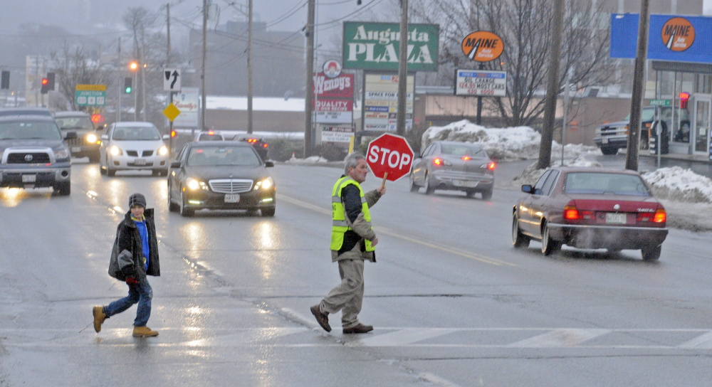 Crossing guard Reggie Gagne has been hired by Augusta schools to help children cross busy Western Avenue following public outcry that a school board subcommittee voted to eliminate all crossing guards across the city.