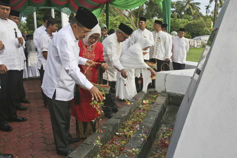 Indonesian Vice President Jusuf Kalla sprinkles flowers during a ceremony commemorating the 10th anniversary of the Indian Ocean tsunami at a mass grave in Aceh Besar, Aceh province, Indonesia, on Friday.
