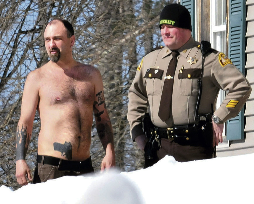 Michael Smith, left, bearing a realistic-looking tattoo of a handgun on his stomach, stands beside a Somerset County Sheriff deputy outside his home in Norridgewock, Maine on March 18. Smith was arrested June 13 after he allegedly showed up at a deputy's home with a real gun in his waistband and drugs in his backpack. He was charged with stealing prescription narcotics from his girlfriend and released from the Somerset County Jail on $1,000 cash bail.