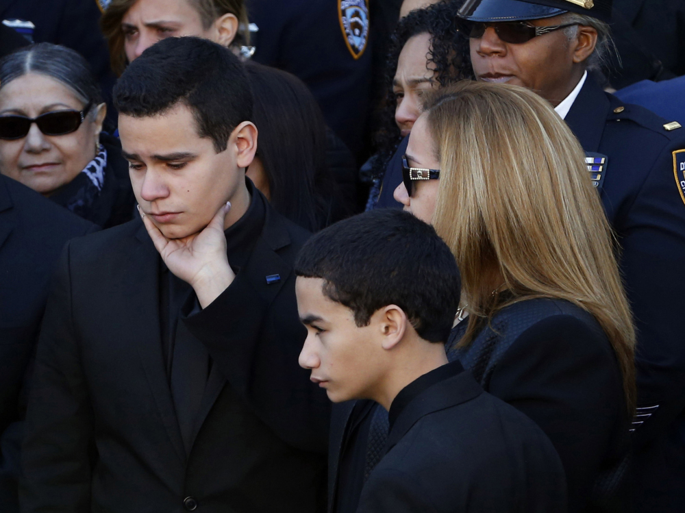 Justin Ramos, the son of slain New York City police officer Rafael Ramos, left, is comforted by his mother, Maritza Ramos, following funeral services at Christ Tabernacle Church, in the Glendale section of Queens, Saturday, Dec. 27, 2014, in New York. Also pictured is officer Ramos' other son, Jaden Ramos, bottom.