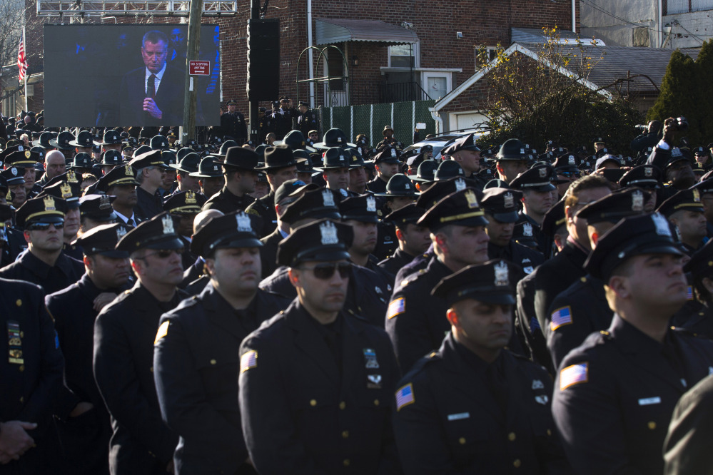 Police officers turn their backs as New York City Mayor Bill de Blasio speaks at the funeral of New York City police officer Rafael Ramos in the Glendale section of Queens, Saturday, Dec. 27, 2014, in New York. Ramos and his partner, officer Wenjian Liu, were killed Dec. 20 as they sat in their patrol car on a Brooklyn street. The shooter, Ismaaiyl Brinsley, later killed himself.