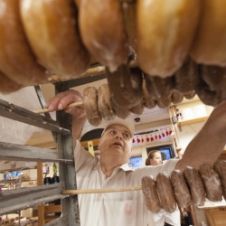 Daryl Buck removes glazed doughnuts from a rack at Hillman's Bakery in Fairfield on Tuesday morning. Buck has worked on and off at bakeries since his high school days. Wednesday was Buck's last day making doughnuts and pastries at Hillman's.