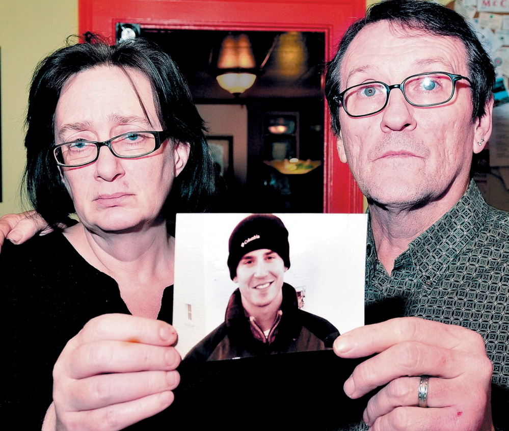 Lorna and Michael Smilek hold a 2006 photograph of Michael's son, Justin Crowley-Smilek, who was fatally shot in a confrontation with Farmington police. Michael Smilek said his son came home from severe combat stress after serving as a U.S. Army Ranger in Afghanistan.