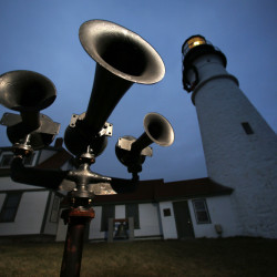 Foghorns that were retired long ago remain aimed toward the sea at Portland Head Light in Cape Elizabeth. The Coast Guard's plan to convert old-style foghorns to newer technology is drawing criticism.