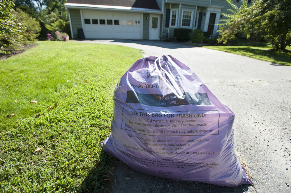 A purple trash bag awaits pick up by disposal personnel along Johnson Heights in Waterville in September. The city's pay-as-you-throw trash disposal system has been a success but has raised the rancor of some who see the purchase of bags as an additional tax.