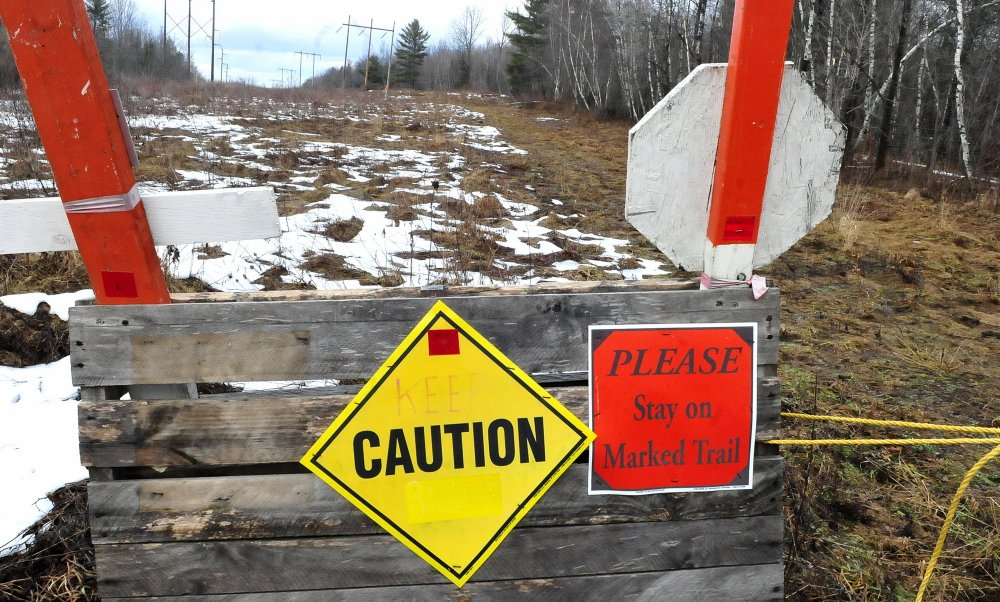 Signs along a snowmobile trail nearly barren of snow warn riders of poor conditions beside the Skowhegan Sno-Hawks club house in Skowhegan. There was no sight of snowmobilers out riding on the unseasonably warm Sunday.