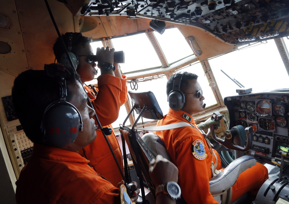 Crew members on an Indonesian Air Force plane search for debris from AirAsia Flight 8501 over Karimata Strait in Indonesia on Monday. The airliner vanished Sunday during stormy weather.