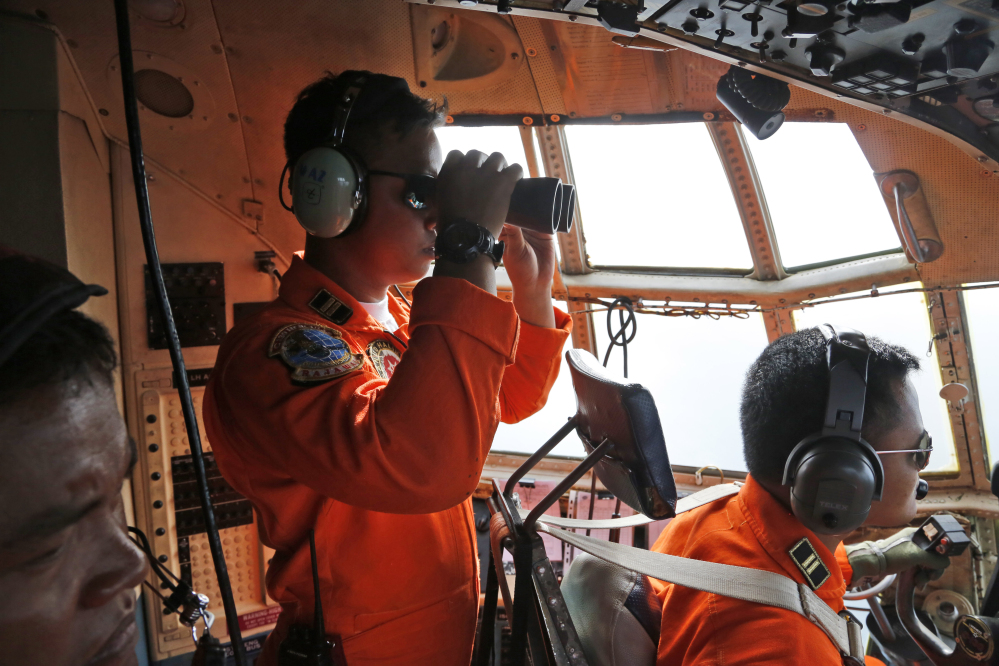 A crew of an Indonesian Air Force C-130 airplane of the 31st Air Squadron uses a binocular to scan the horizon during a search operation for the missing AirAsia flight 8501 jetliner over the waters of Karimata Strait in Indonesia, Monday. Search planes and ships from several countries on Monday were scouring Indonesian waters over which an AirAsia jet disappeared, more than a day into the region's latest aviation mystery.