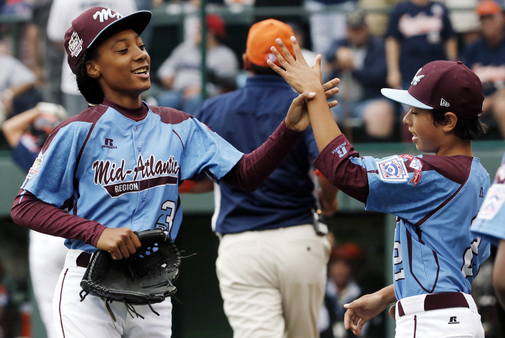 In this Aug. 15, 2014, file photo, Pennsylvania pitcher Mo'ne Davis, left, celebrates with teammate Jack Rice (2) after getting the final out of a 4-0 shutout against Tennessee during a baseball game in United States pool play at the Little League.