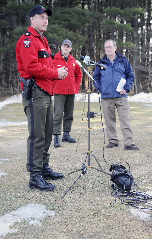 Standing on bare ground, Warden Service Maj. Chris Cloutier speaks Monday in Augusta about the need to ride snowmobiles safely this winter. At center is Warden Service Cpl. John MacDonald and Maine Snowmobile Association Executive Director Bob Meyers.