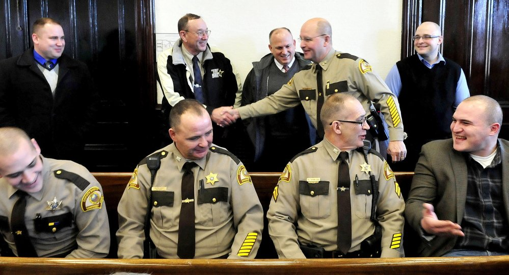 Dale Lancaster, right, shakes hands with retiring Penobscot County Sheriff Glenn Ross beside dozens of officers from several departments prior to a swearing-in ceremony as the new Somerset County Sheriff in Skowhegan on Monday.