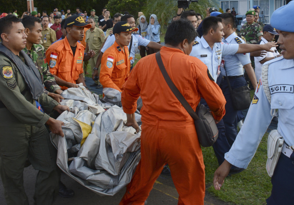 Indonesian Air Force personnel carry airplane parts recovered from the water near the site where AirAsia Flight 8501 disappeared, at the airbase in Pangkalan Bun, Central Borneo, Indonesia.