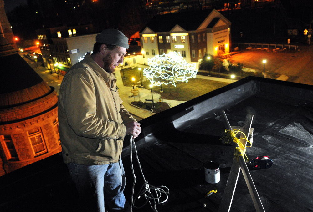 Working on the roof setting up the ropes, Jason McFarland prepares to raise the New Year's Eve ball on Tuesday at Gagliano's Bistro on Water Street in Augusta.
