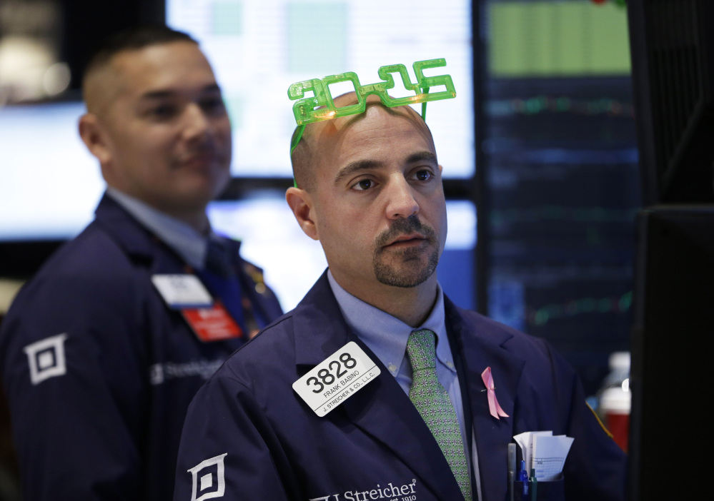 A trader wears glasses in the shape of 2015 while working on the floor at the New York Stock Exchange in New York on Wednesday.
