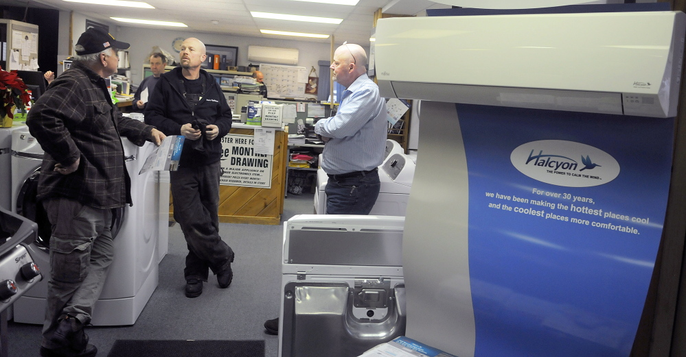 Dave's Appliance co-owner Mike Ketchen, center, confers with customer Larry Labreck, left, and salesman Ed Pritchard at the Winthrop appliance store on Dec. 23. Labreck was shopping for a heat pump. Ketchen owns the business with his brothers, Scott and Brian.