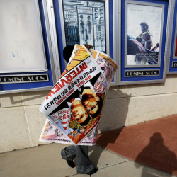 "A worker carries away a poster for the movie ""The Interview"" after pulling it from a display case at a Carmike Cinemas movie theater in Atlanta on Wednesday. The Associated Press"