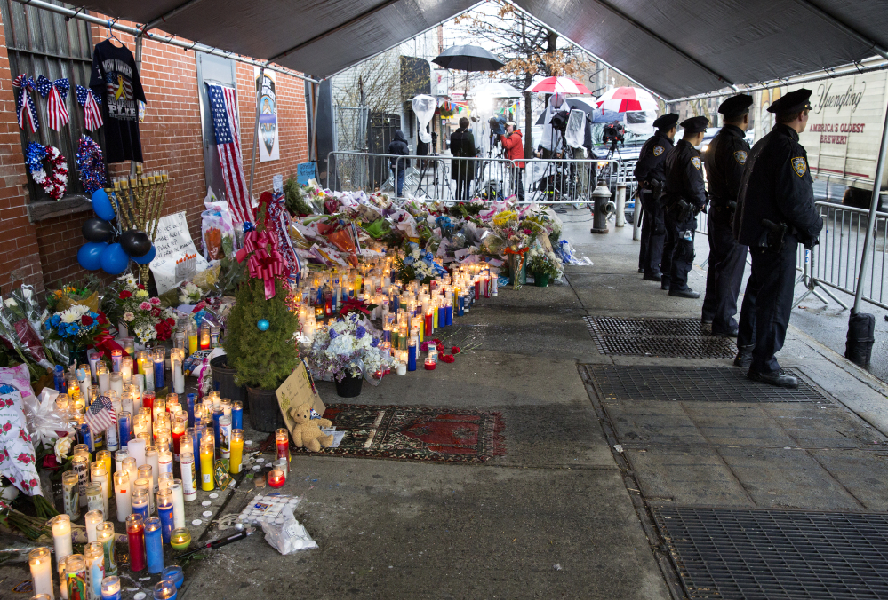New York City police officers stand at a makeshift memorial Tuesday, near where two fellow police officers, Rafael Ramos and Wenjian Liu, were shot and killed in an apparent ambush in the Brooklyn borough of New York. The Associated Press