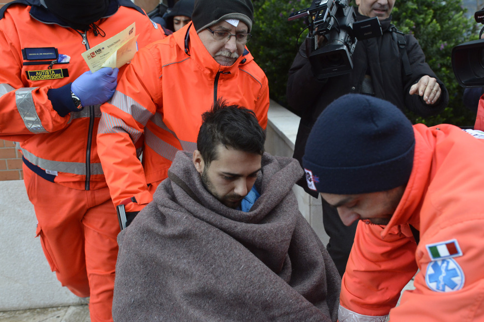 Rescuers assist a passenger of the Italian-flagged Norman Atlantic, that caught fire in the Adriatic Sea, in Bari harbor, southern Italy, Monday. A ferry carrying nearly 500 people caught fire off the Greek island of Corfu early Sunday, trapping passengers on the top decks as gale-force winds and choppy seas hampered the evacuation. The Associated Press