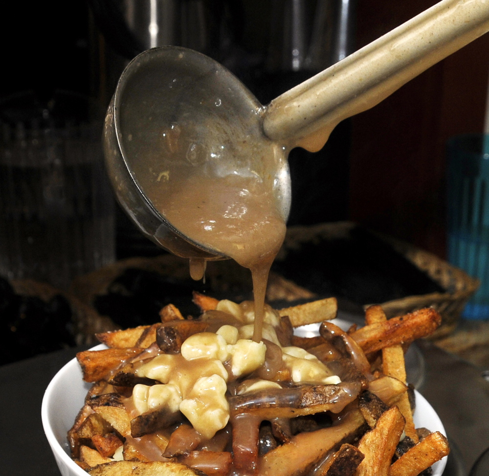 Duckfat's poutine begins with its signature fries, topped with cheese curds and gravy. Gordon Chibroski/Press Herald File