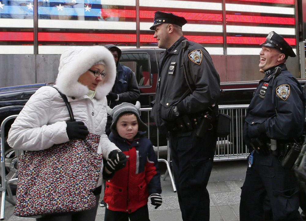 A woman and a child make their way through Times Square as New York City police officers share a laugh while patrolling the streets on Tuesday.
