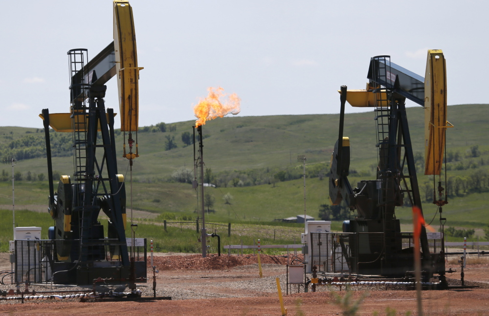"""Methane flares off an oil well in North Dakota above. A methane """"hot spot"""" in New Mexico is as large as the state of Delaware according to NASA. The gas will likely be a flashpoint as the government tries to regulate leaks in the new year. The Associated Press"""