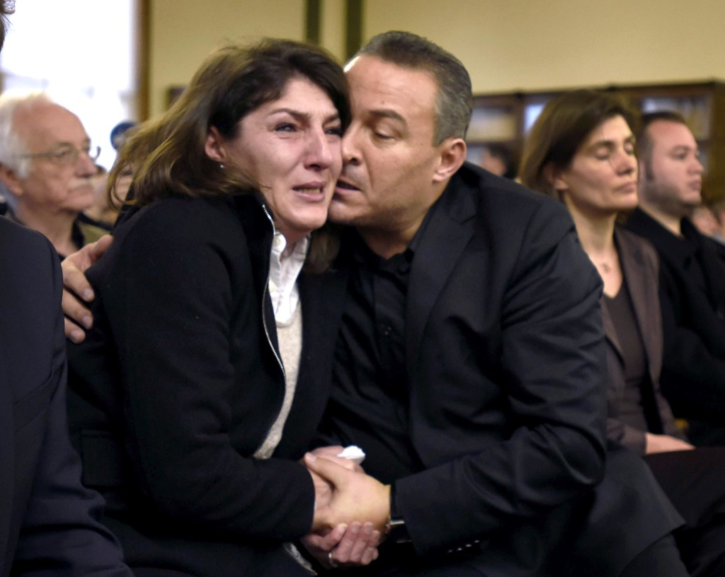 Gulcin and Celal Dede embrace after Markus Kaarma was found guilty of deliberate homicide, Wednesday, Dec. 17, 2014, in Missoula County District Court in Missoula, Mont., in the shooting death of their son Diren Dede, a foreign exchange student from Germany. The Associated Press