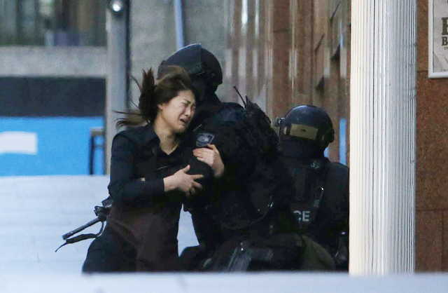A hostage runs towards a police officer outside Lindt cafe, where other hostages are being held, in Martin Place in central Sydney Monday.