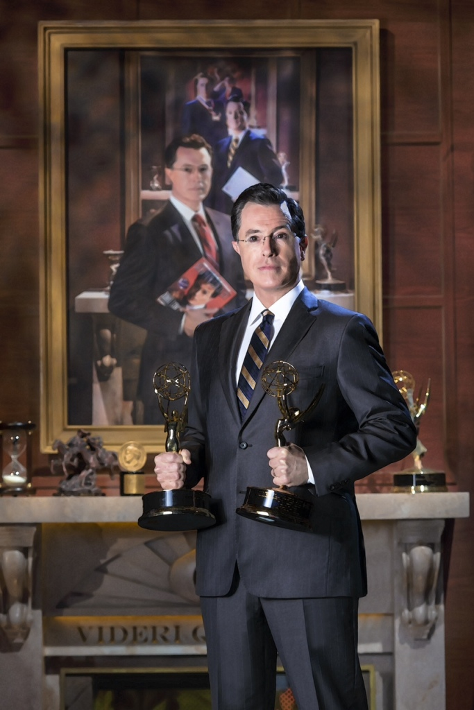 Stephen Colbert poses in front of his portrait in this photo provided by the Smithsonian. The portrait will be installed Friday and be displayed through April 19, once again between the bathrooms and above a water fountain. The Associated Press