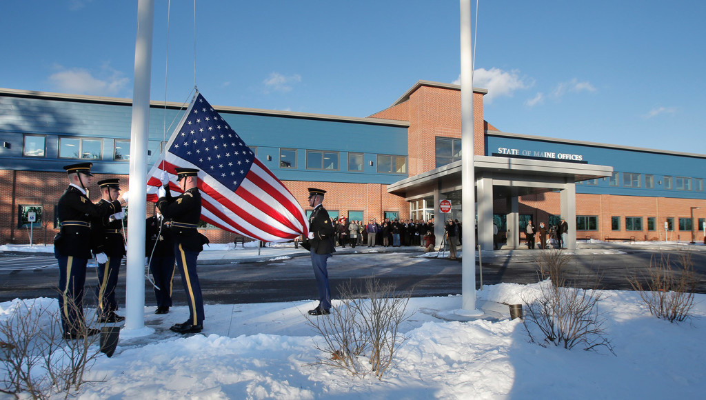 A military honor guard raises a flag Monday outside the new offices of the Department of Health and Human Services and Department of Labor in South Portland . The new building also houses regional offices of the Department of Veterans' Affairs. Gregory Rec/Staff Photographer
