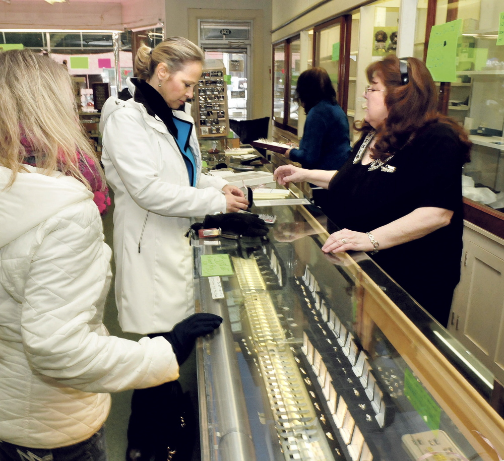 Trask Jewelers manager Beth Neeley, right, shows rings to customer Kathy Clark on Wednesday, the last day the Farmington business was open.