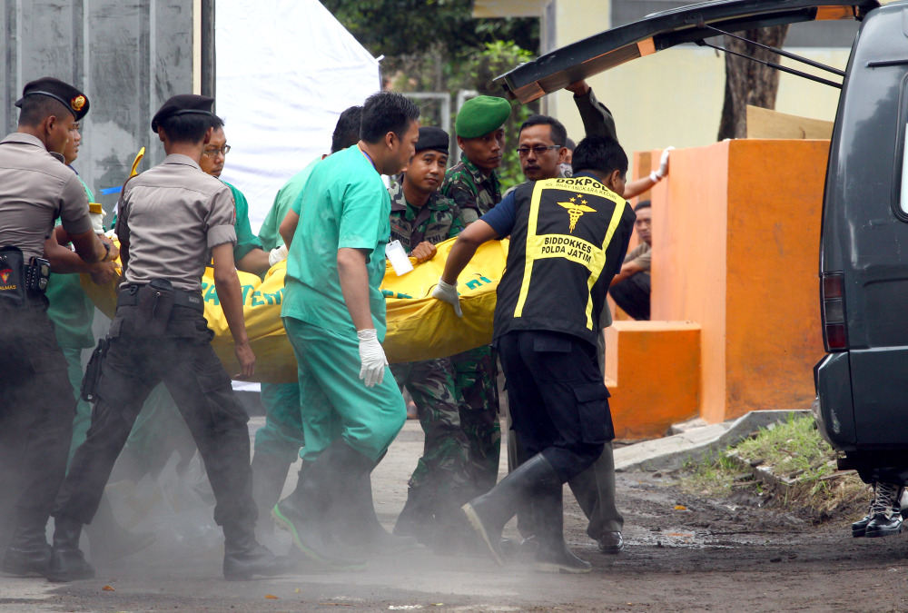 Indonesian police, military and medical workers carry a body bag holding a victim of AirAsia Flight 8501 for identification at Bhayangkara Police Hospital in Surabaya, Indonesia, on Saturday. After nearly a week of searching for victims, rescue teams had their most successful day yet, more than tripling the number of bodies pulled from the Java Sea, some still strapped to their seats.
