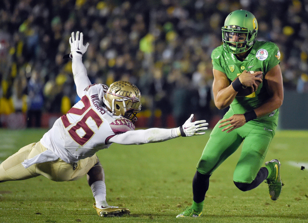 Oregon quarterback Marcus Mariota, right, scores past Florida State defensive back P.J. Williams during the second half of the Rose Bowl on Thursday in Pasadena, Calif. Oregon will meet Ohio State in the national championship game on Jan. 12.