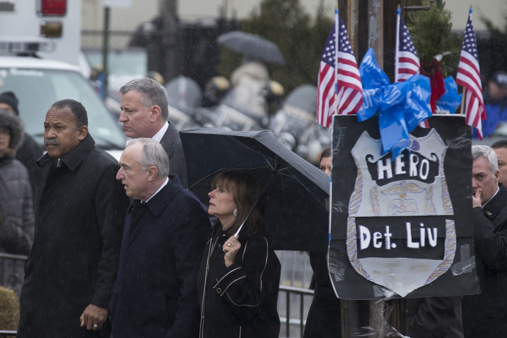 From left, 1st New York Police Department Deputy Commissioner Benjamin Tucker, New York City Mayor Bill de Blasio, upper, New York Police Department Commissioner Bill Bratton, and Rikki Klieman, Bratton's wife, arrive at the wake of NYPD Officer Wenjian Liu at Aievoli Funeral Home, Saturday.