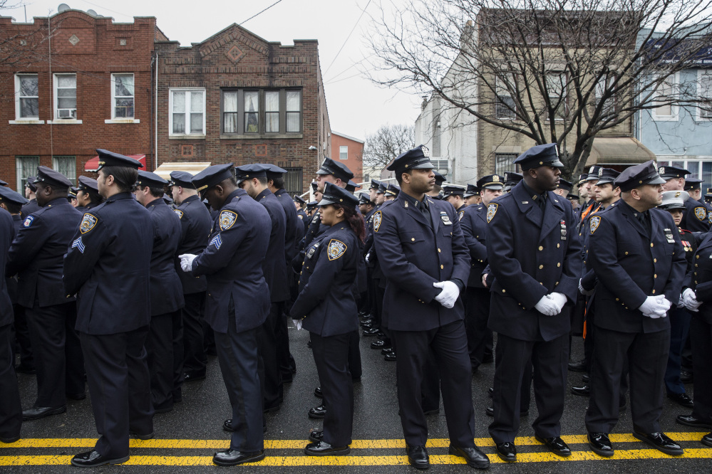 Police officers turn their backs as Mayor Bill de Blasio speaks during the funeral of New York Police Department Officer Wenjian Liu at Aievoli Funeral Home, Sunday, Jan. 4, 2015, in the Brooklyn borough of New York. Liu and his partner, officer Rafael Ramos, were killed Dec. 20 as they sat in their patrol car on a Brooklyn street. The shooter, Ismaaiyl Brinsley, later killed himself. (AP Photo/John Minchillo)