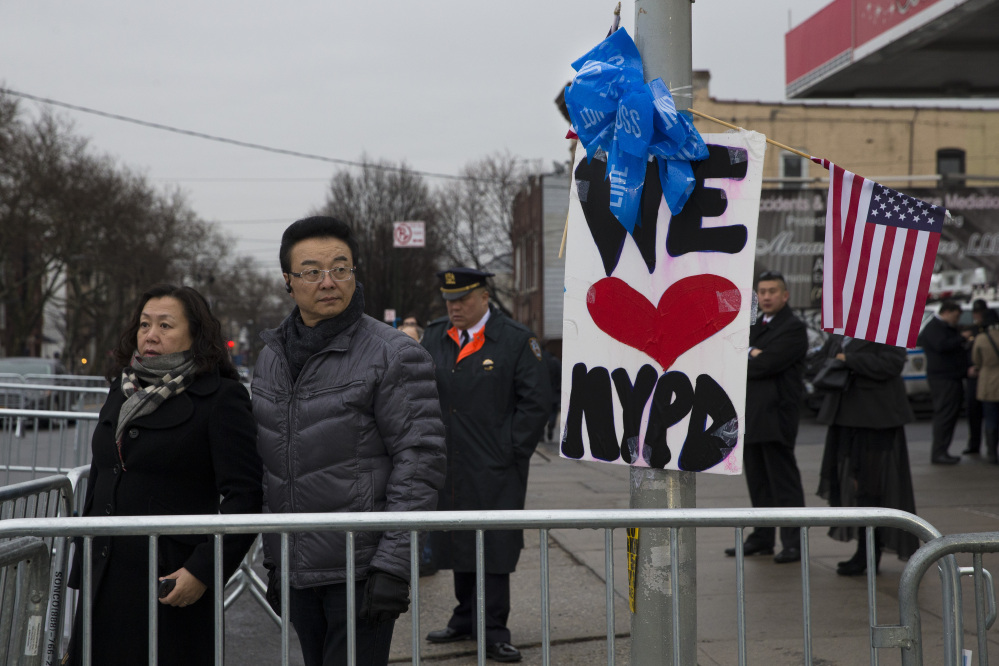 Pedestrians pause outside the funeral of New York Police Department officer Wenjian Liu at Aievoli Funeral Home, on Sunday, in the Brooklyn. Liu and his partner, officer Rafael Ramos, were killed Dec. 20 as they sat in their patrol car on a Brooklyn street. The shooter, Ismaaiyl Brinsley, later killed himself.
