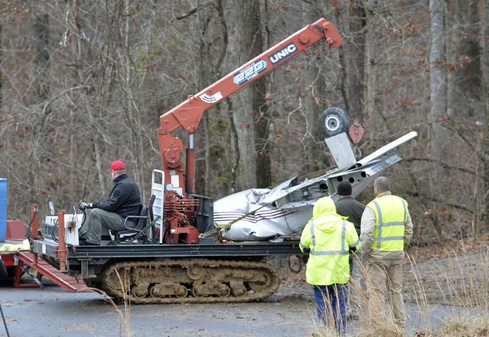 Salvage workers bring out part of a Piper PA-34's fuselage, wing, and landing gear from a crash site Sunday in Kuttawa, Ky. The plane went down in a deeply wooded area and special machinery was required to remove it.