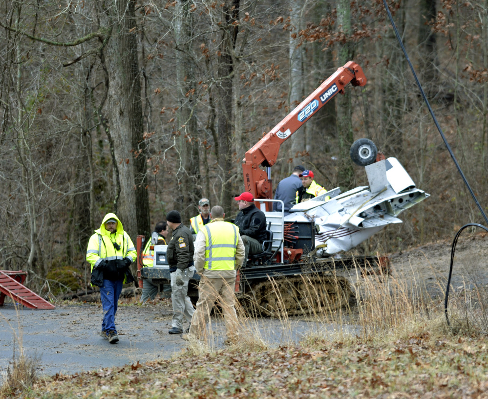 Salvage workers bring out part of a Piper PA-34's fuselage, wing, and landing gear from a crash site Sunday in Kuttawa, Ky.