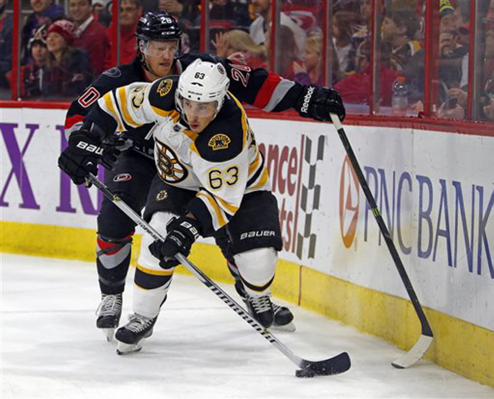 Boston Bruins' Brad Marchand battles with Carolina's Riley Nash (20) in Sunday's game at Raleigh, N.C. The Hurricanes won 2-1 in a shootout.