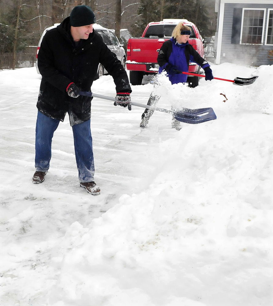 Working as a team, Peter and Lisa Hallen shovel snow at their home in Waterville on Sunday.