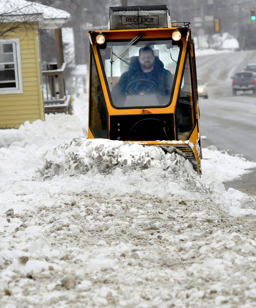 Waterville Public Works employee Kirk Lachance clears sidewalks of the snow that fell on Sunday.