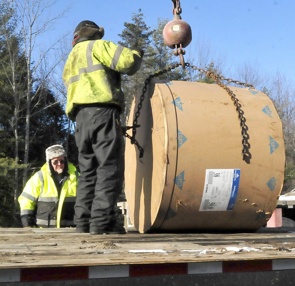 Workers on Monday load rolls of paper after using a crane to unload a tractor-trailer that slid and overturned on the northbound lane of I-95 in Sidney earlier Monday. Traffic was detoured from exit 113 to exit 120.