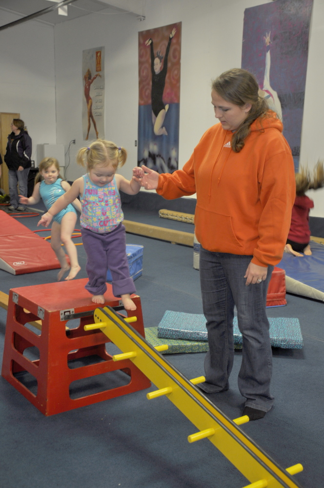 Mary Chase helps her 21-month-old daughter Emerson on a balance apparatus during an open house at Decal Gymnastics in Skowhegan Saturday. The Skowhegan Parks and Recreation gymnastics programs will now be held at the 19 Waterville Road facility.