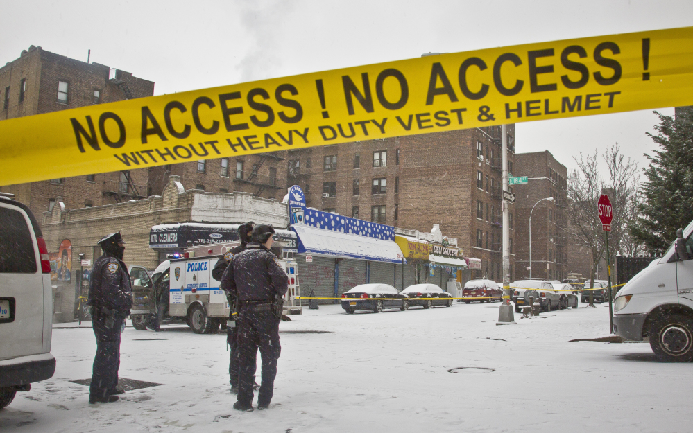 Police stand guard Tuesday at the area where police and suspects exchanged gunfire the night before in the Bronx borough of New York. A manhunt was under way Tuesday for at least two suspects who shot and wounded two New York City plainclothes police officers responding to a robbery late Monday.