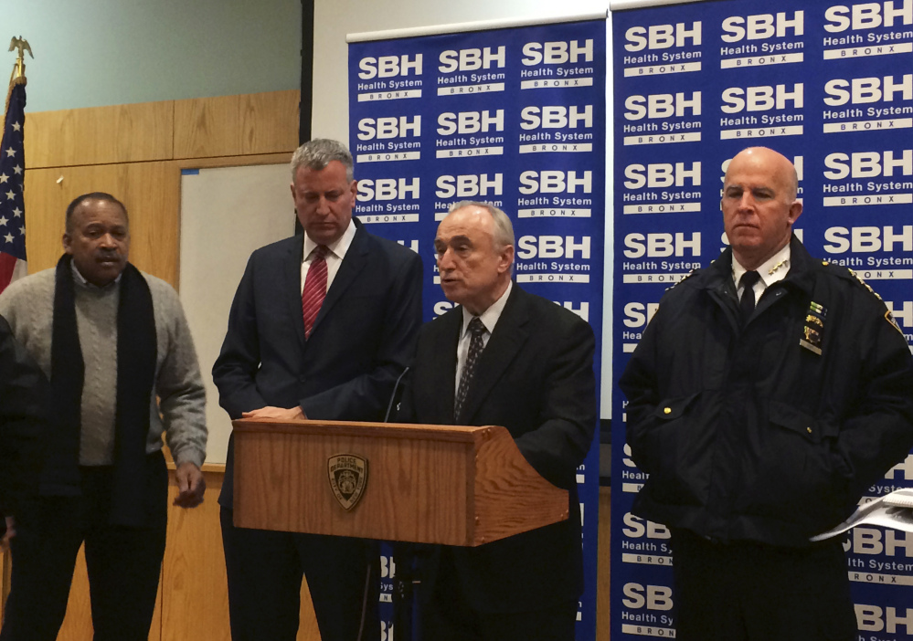 New York City Mayor Bill de Blasio, second left, stands by as New York Police Department Commissioner William Bratton, second right, speaks at a news conference at St. Barnabas Hospital in the Bronx section of New York, early Tuesday, after two New York City police officers were shot late Monday night.