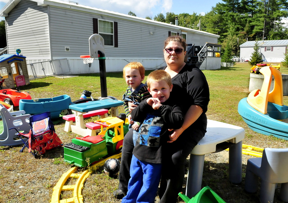 """Dawn Zammuto holds her grandchildren Allen, left, and Dominic outside the home she rents in Norridgewock on Sept. 17, 2014. Zammuto was threatened with eviction by the home's owner, who claimed she violated a """"no pet"""" rule because she allowed her daughter and her daughter's service dog to stay a few days in August."""
