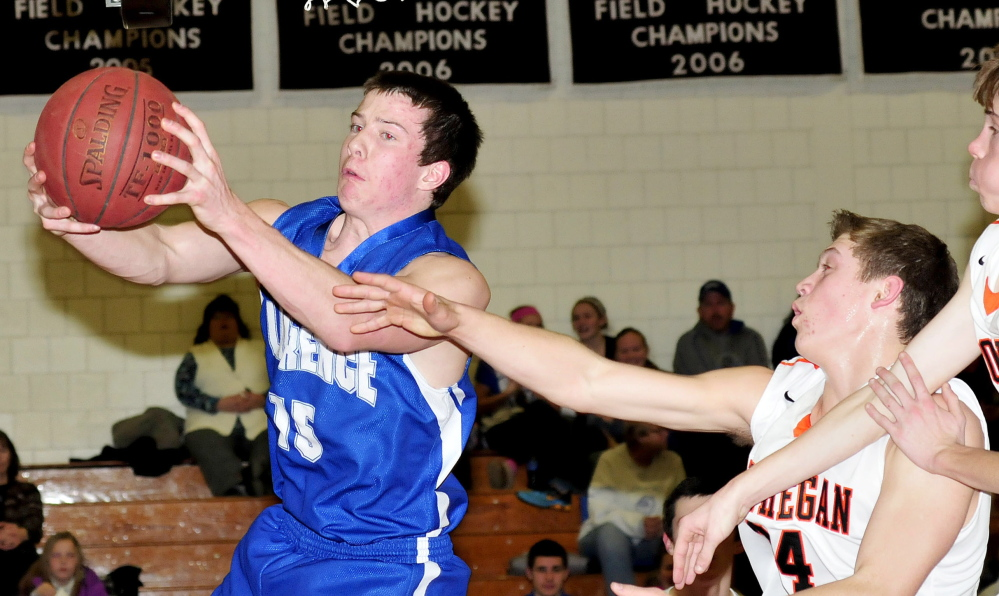 Lawrence's Seth Powers, left, is blocked by Skowhegan's Garrett McSweeney during game Tuesday in Skowhegan. Lawrence won 70-56.