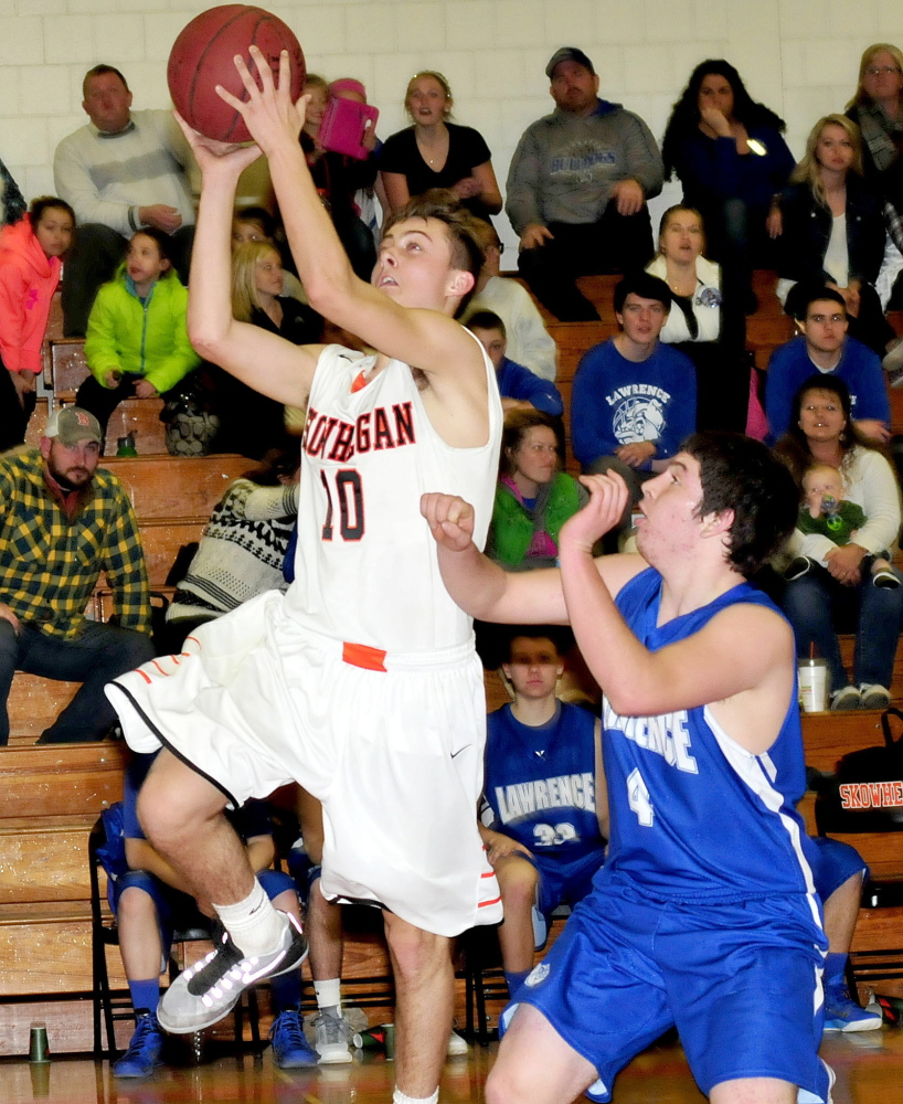 Skowhegan's Kyle Dugas goes up with ball against Lawrence's Kyle Robinson during a game Tuesday in Skowhegan.