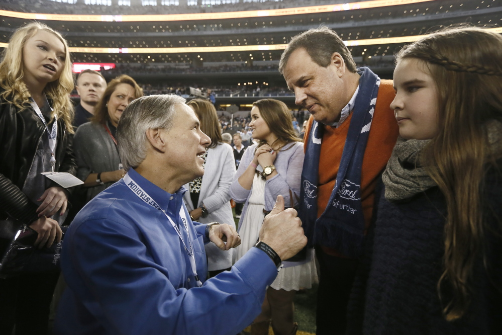 Texas Gov.-elect Greg Abbott, left, speaks with New Jersey Gov. Chris Christie, right, before a game between the Dallas Cowboys and Indianapolis Colts in December in Arlington, Texas. Christie has brushed off criticism that he has attended several games on the tab of the team owner.
