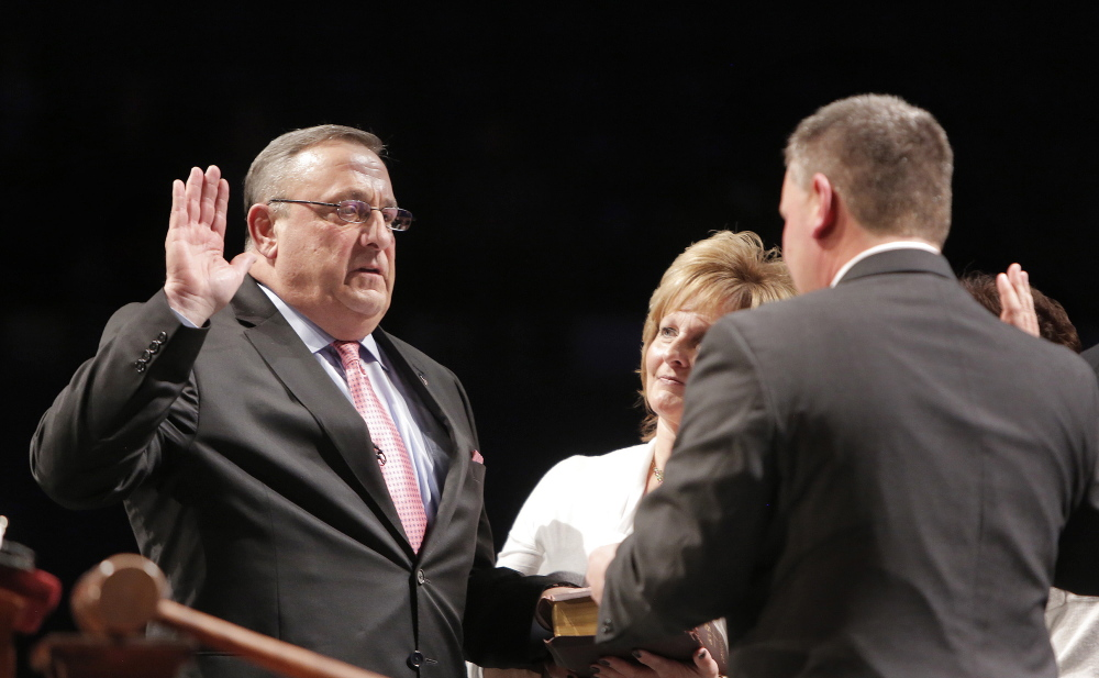 Maine Senate President Michael Thibodeau administers the oath of office to Gov. Paul LePage, who is joined by his wife, Ann. The governor said his decisive election victory translates into voter endorsement of his policies.